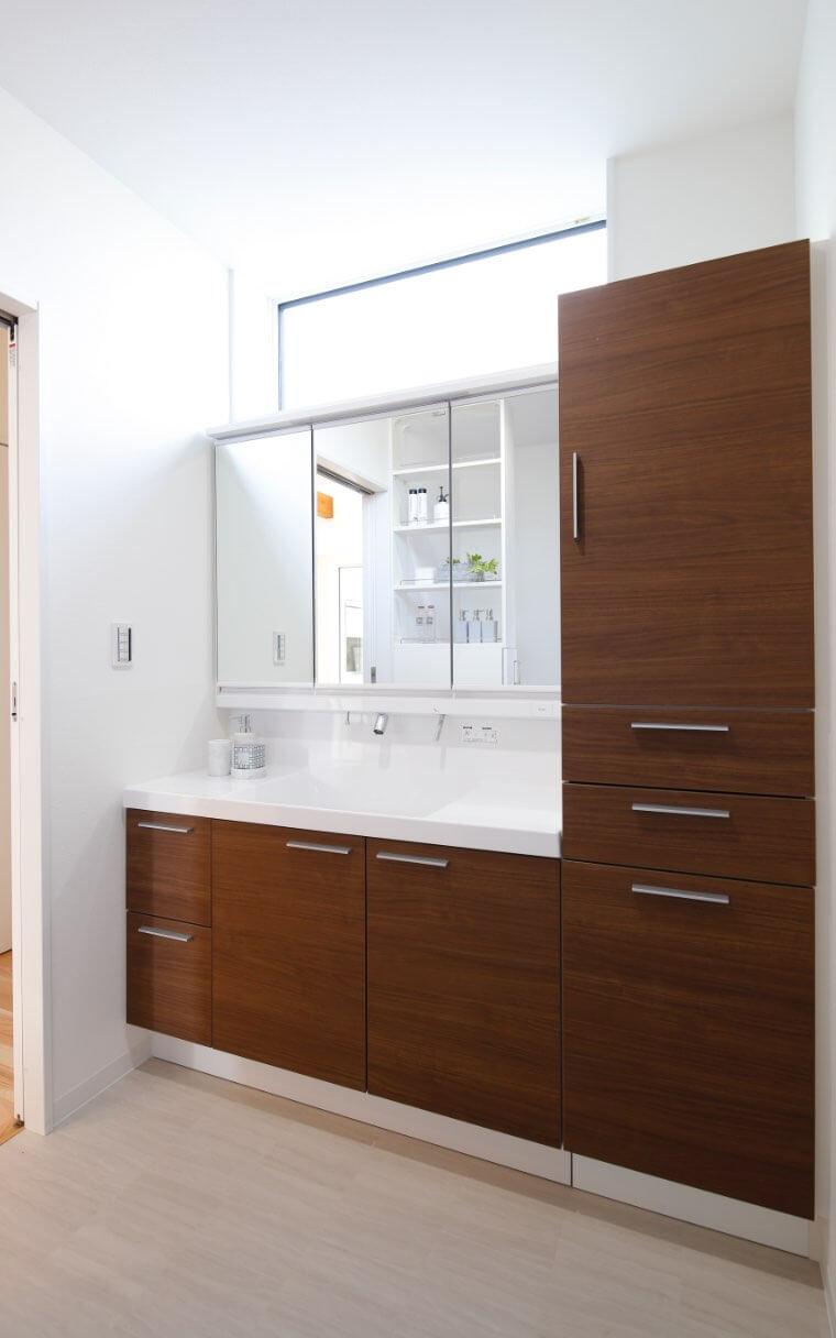 シックな木目調の洗面台。収納力たっぷりで使い勝手が良く、洗面台の後ろにはシャンプーなどを収納できる棚も設置しております。