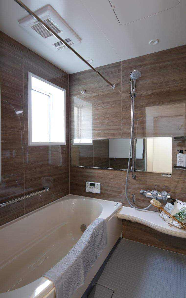 疲れた心をほぐす木目調の浴室。鏡を横長にすることで空間に奥行をもたらし、広々としたバスルームを演出しています。